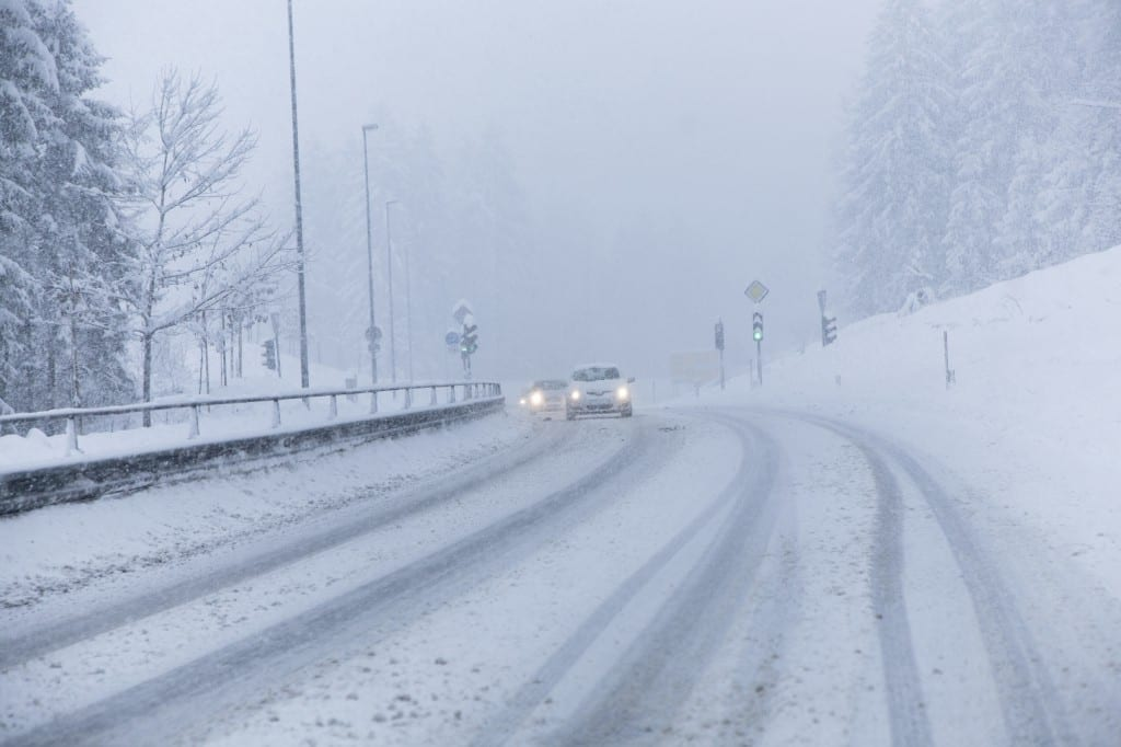 car driving in whiteout, blizzard, snow