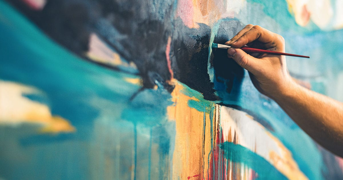 Close-up of hand painting large turquoise and yellow painting