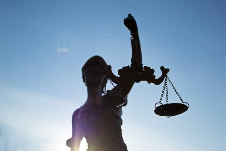 The silhouette of Lady Justice appears against a blue sky.