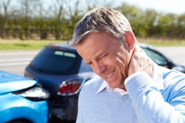 Man in blue sweater holding neck in pain after a rear-end car accident