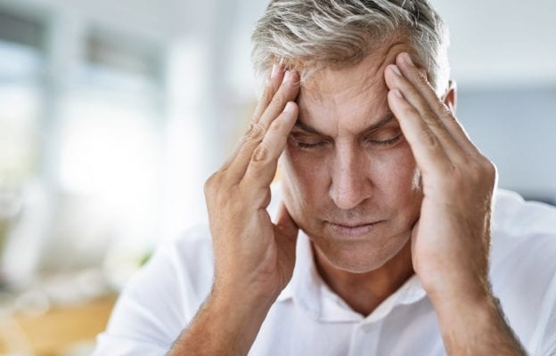 Man with grey hair wearing white shirt closing eyes and rubbing forehead in discomfort