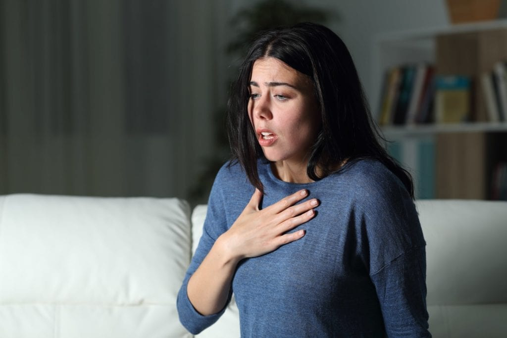 Woman in blue long sleeve shirt in living room holding chest and gasping for air