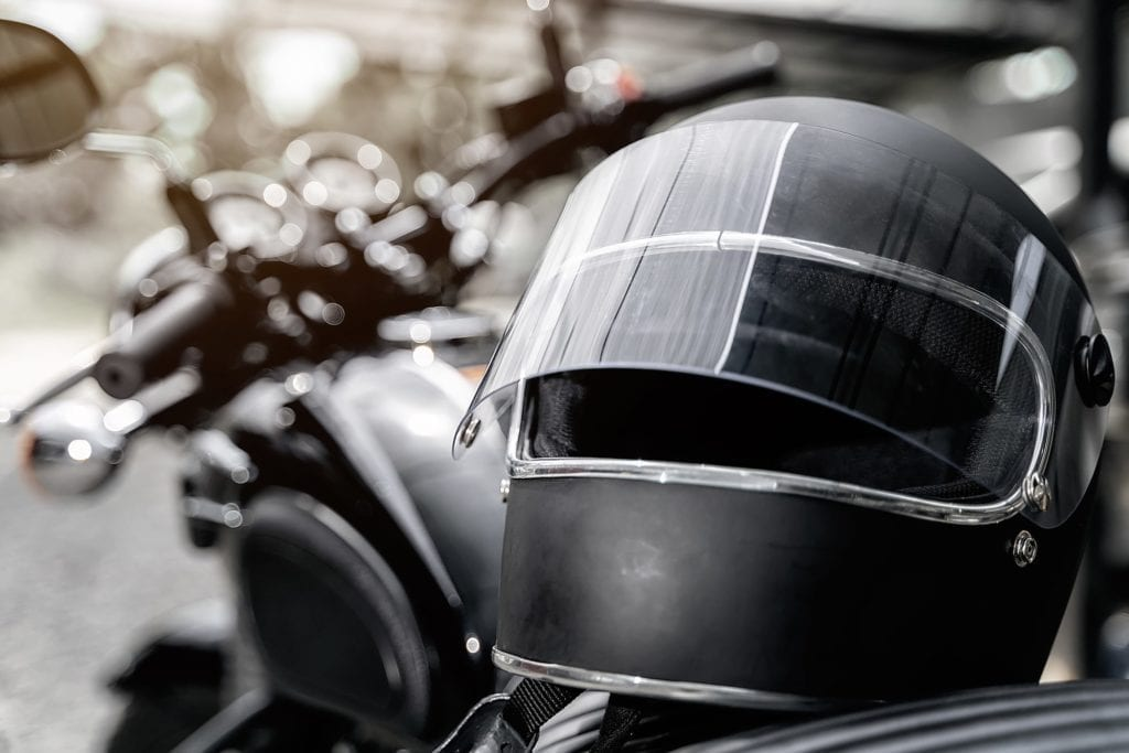 Black motorcycle helmet resting on motorcycle seat