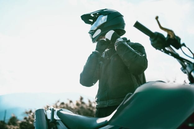 Motorcylists wearing black jacket and gloves putting helmet on