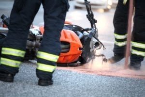 Orange motorcycle downed after accident with first responders standing near it