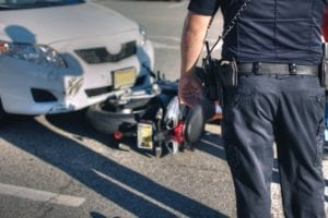 Downed motorcycle struck by white car with police officer examining the scene