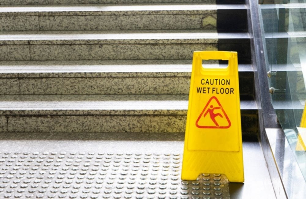 """A yellow """"Wet floor"""" sign sits at the bottom of granite stairs. Slip and fall accidents at work are a leading cause of workers compensation and brain injury claims."""