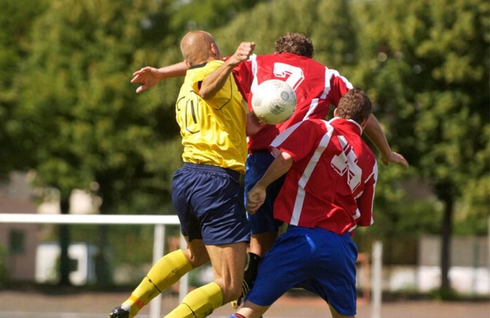 An image of three men colliding in the air during a soccer game. Head injuries from sports can lead to TBI and even epilepsy.