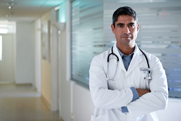 A doctor in a lab coat stands in the hallway with his arms crossed, looking at the camera. Doctors can be held liable for medical malpractice.