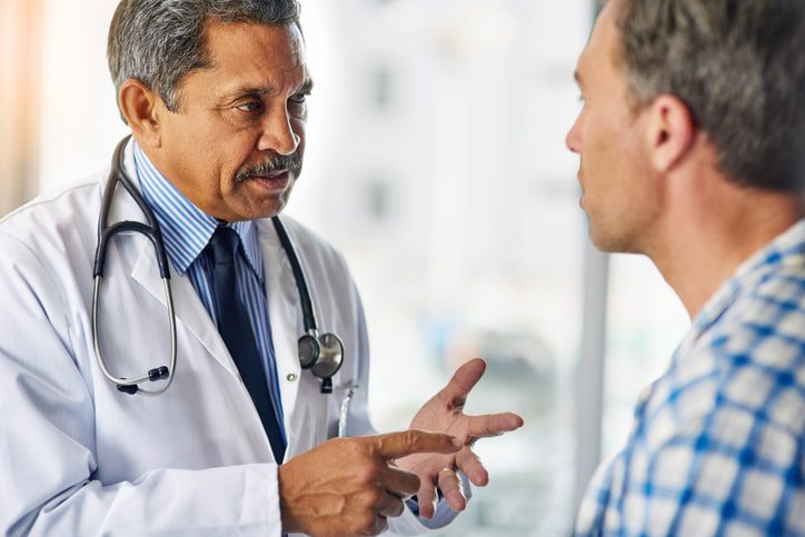 A latino doctor wearing a lab coat and stethescope consults with a patient. Misdiagnosis by a doctor can be grounds for a medical malpractice lawsuit.