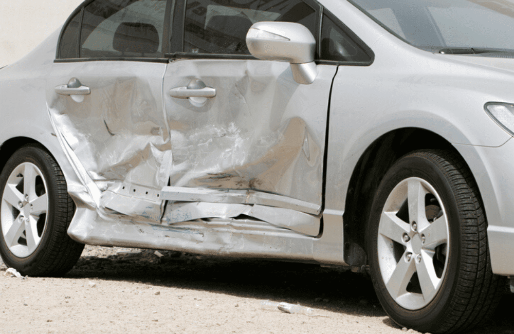 Dangerous intersections are the site of serious car accidents and can result in car damage like this - the passenger side of a silver car is shown with severe impact damage to both doors.