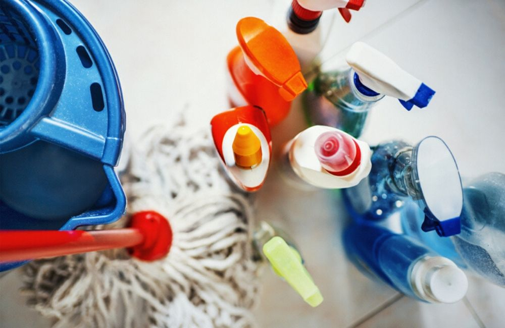 A photo shows a traditional mop, bucket, and several spray bottles of different cleaners. Product liability lawsuits can include common household products such as these.