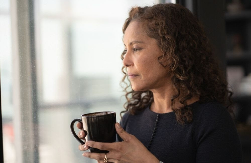 A dark-featured woman with curly hair holds a mug as she looks out her window, deep in thought. Spouses are considered first when wrongful death settlements are paid out.