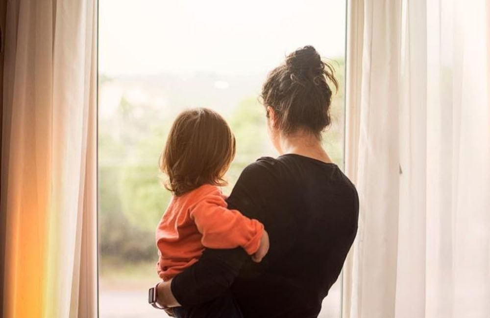 A widowed young woman holds her son as they look out the window with their backs turned. A wrongful death law firm can help you understand how much your settlement may be worth.