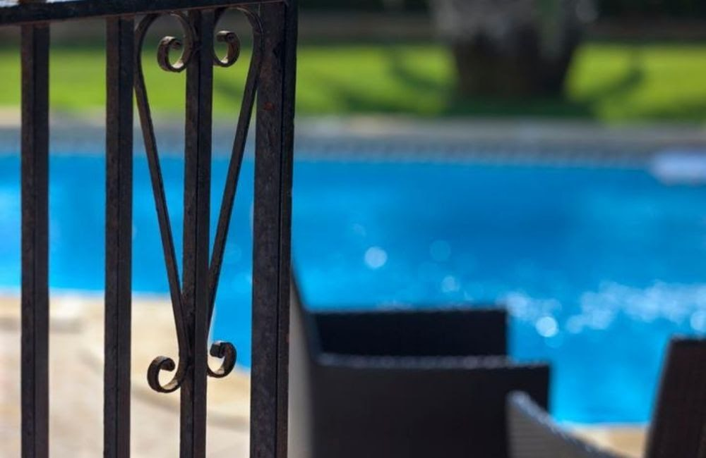 Closeup shot of an open gate around a swimming pool. Small children often drown when gates are left open around swimming pools, which can be cause for a wrongful death lawsuit.