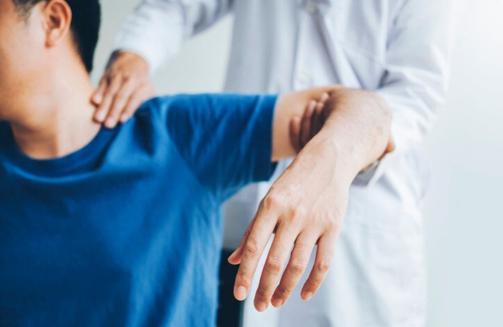A doctor examines a man in a blue shirt for whiplash injuries with one hand lifting his arm and the other on his neck.