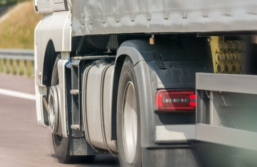 A shot from the side rear of a semi-truck on a freeway shows the underside of the truck body. A Virginia truck accident lawyer can help you receive compensation for injuries after a collision.