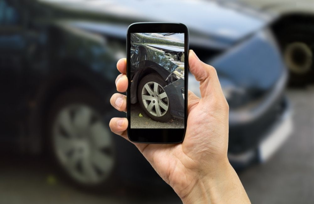 A closeup shot of a person holding their smartphone up, showing an image of the damaged vehicle in the background.
