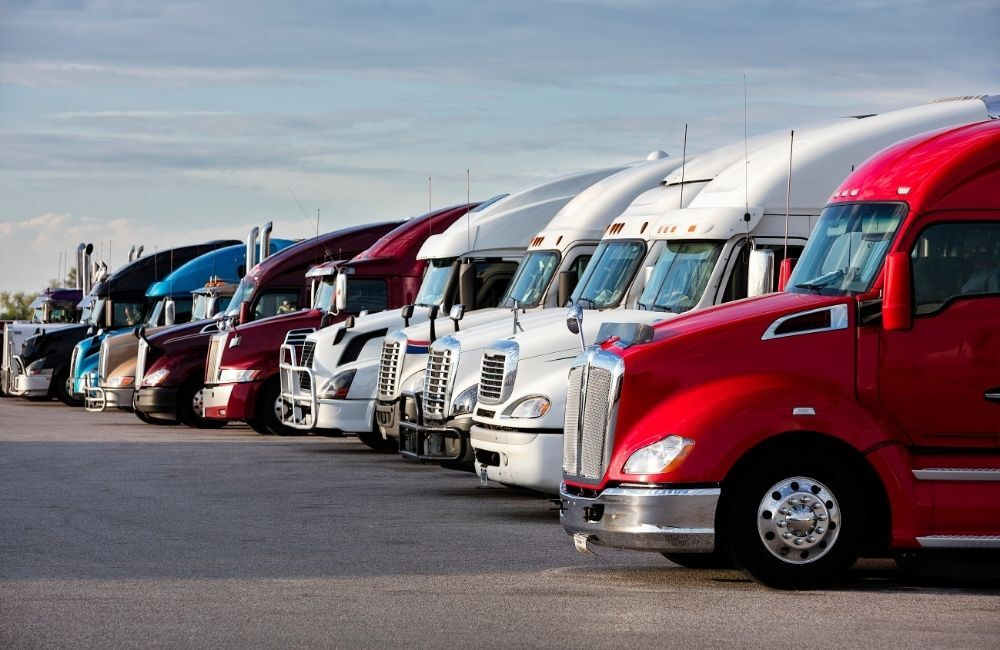 A row of parked 18-wheeler trucks is shown from the front side view. Multiple parties can be named in a truck accident lawsuit, including trucking companies.