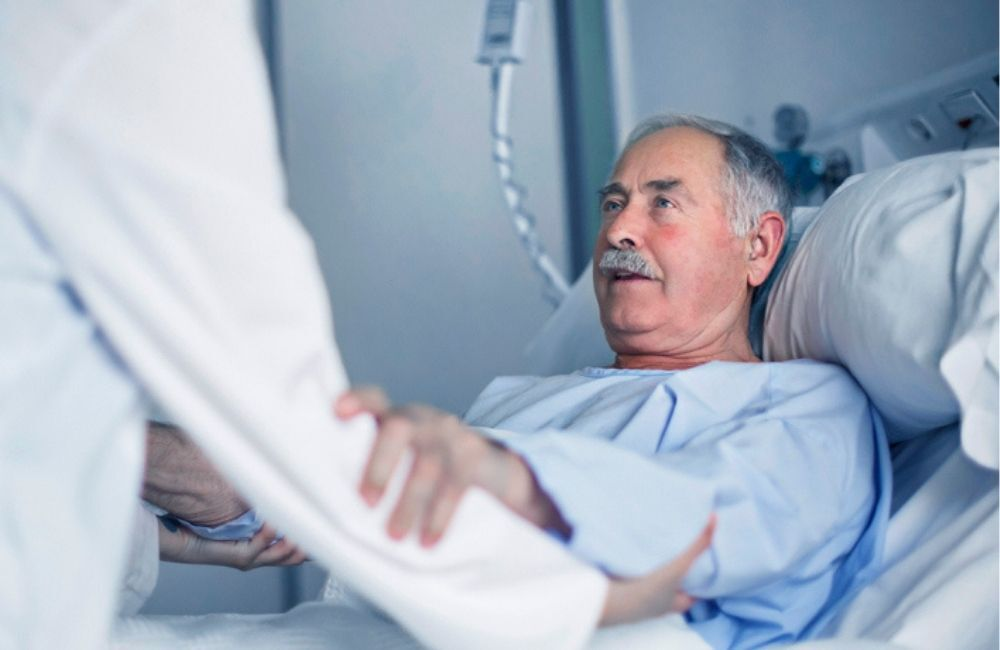A gray haired man receives help from a doctor moving from his hospital bed. Compensation from a truck accident settlement can cover the cost of medical care.