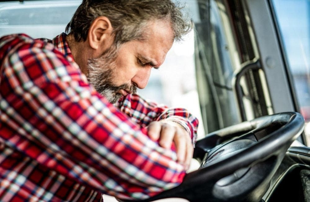 A middle-aged white man rests on the steering wheel of an 18-wheeler truck. Truck driver fatigue is a known cause of serious road accidents.
