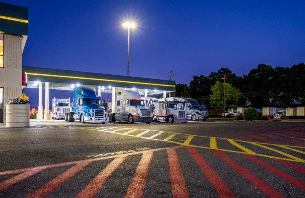 A row of big rig trucks are shown at fuel pumps outside a truck stop at night.