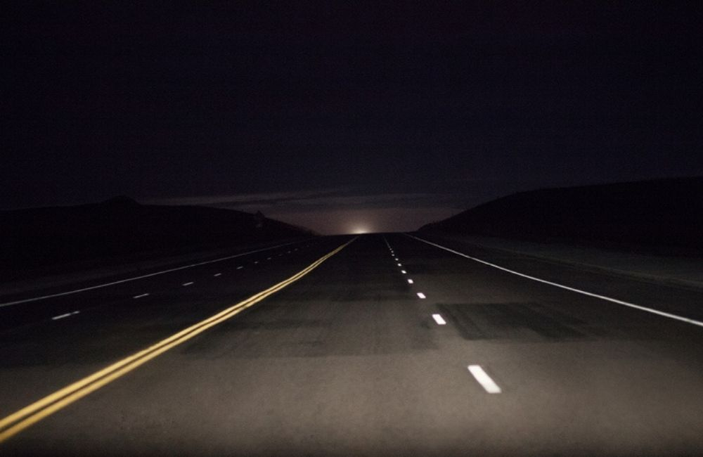 Headlights illuminate an empty four-lane road at night. Driver fatigue has been linked to 13% of roadway accidents.