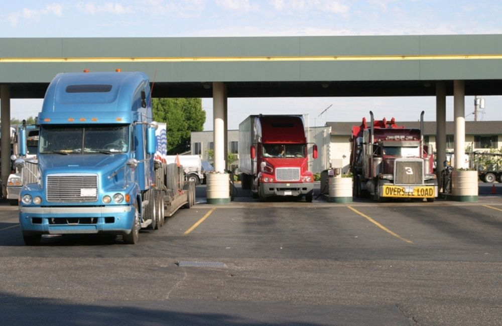 Tractor trailers are shown from the front side fueling up at a rest stop during the afternoon.